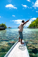 A Man Fishing With Spear on wooden Boat With Beautiful Crystal C