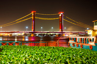 A view of Jembatan Ampera Bridge at night with water hyacinth in